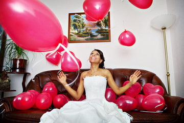 Happy bride is playing with red balls