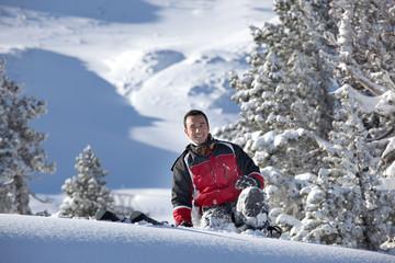 Jeune homme souriant à la neige
