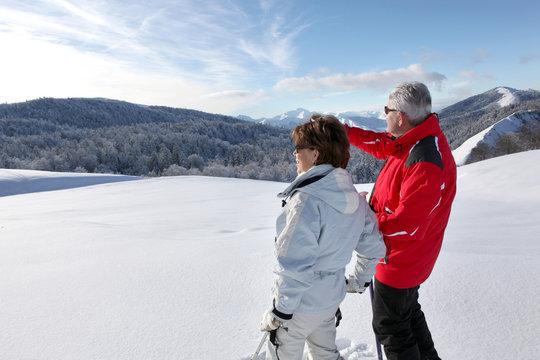 Homme et femme seniors regardant au loin à la neige
