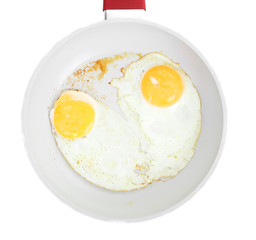 Broken egg frying in a pan isolated on white