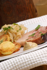 Schweinebraten mit Sauerkraut und Röstkartoffeln