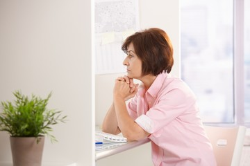 Mature female office worker thinking at desk
