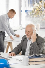Senior businessman talking on landline phone
