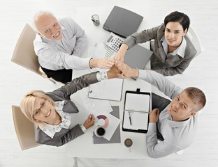 Businessteam raising hands together at meeting