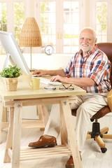 Portrait of elderly man with computer