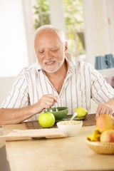 Happy senior man having tea in kitchen