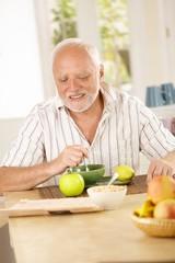 Happy senior man having tea in kitchen