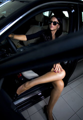 Luxury woman with long legs in the car