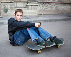 The teenager sits on asphalt with a skateboard