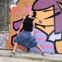 Jeune femme dansant devant un mur couvert de graffitis