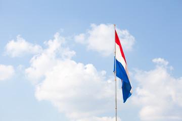 Dutch flag against the blue sky