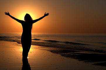 Young adult female with arms wide open on a sunset