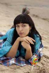 Молодая женщина на пляже осенью ест конфеты леденцы