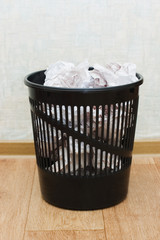 Black plastic basket with garbage indoors