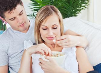 Portrait of a caucasian couple relaxing eating pop corn