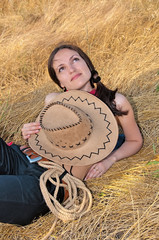 beautiful woman lying in the straw with the hat