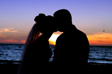 Silhouette of bride and groom kissing on the beach