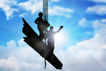 Two men standing on iron bars held up by mega crane