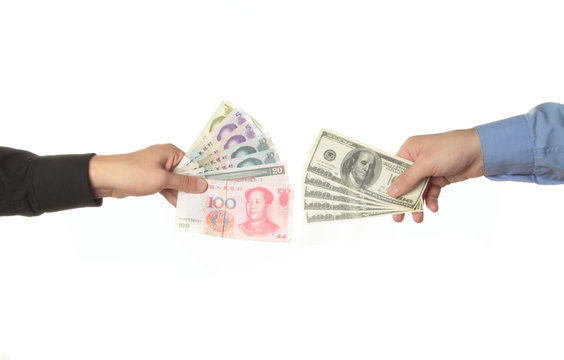Hands holding yuan and dollar bills