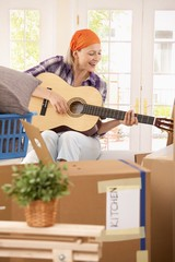 Smiling woman with guitar at moving