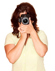 Woman using a professional camera on a white background