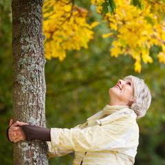 ältere frau umarmt baum
