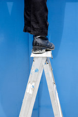 man in dark clothes standing on metal ladder