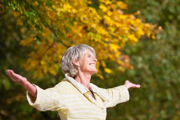 seniorin genießt die sonne im herbst