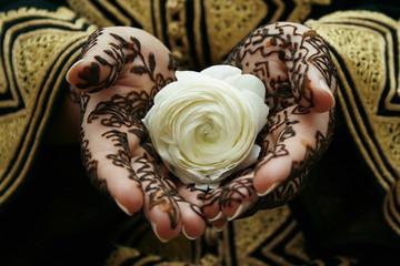 Henna hands holding a flower