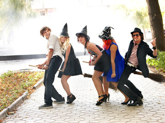Group of people in witck hat on broomstick.