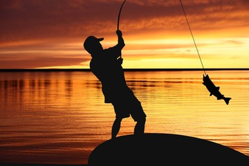 fisherman with a catching fish on sunrise background