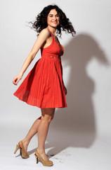 junge Frau tanzt glücklich in einem roten Kleid