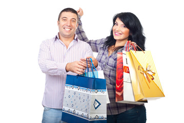 Couple with shopping bags cheering