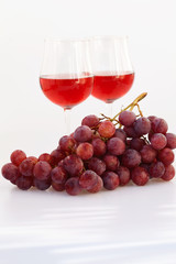 glass of wine and a bunch of grapes isolated on white