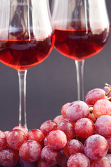 glass of wine and a bunch of grapes on a black background