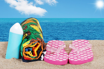 closeup beach with sandals towel and suntan lotion