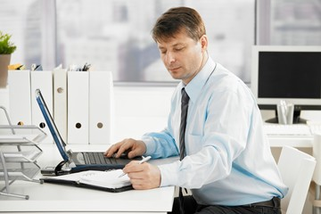 Businessman searching in personal organizer