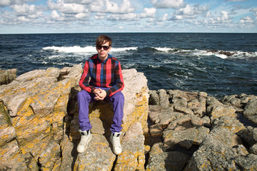 young man sitting on rocks