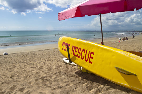 Yellow surf rescue board on the beach under red umbrella