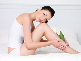 Woman with white tulip on a perfect legs