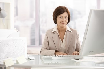 Portrait of senior businesswoman at office desk
