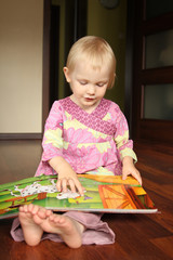 2 years old girl reading or browse through pop-up book.