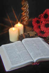 Student studying Bible at christmas by candlelight