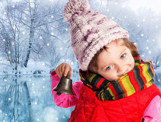 little girl holding christmas bell and winter landscape