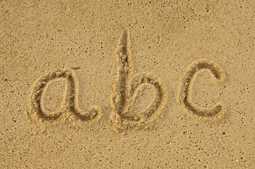 alphabet letters a b c handwritten in sand on beach