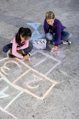 Girls playing with sidewalk chalk