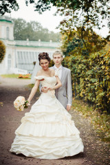 Portrait of newlyweds walking in moscow estate