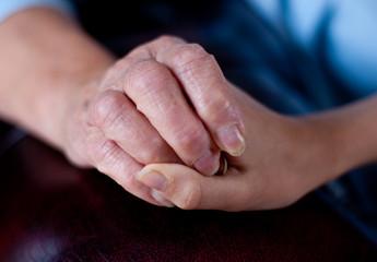 enfant qui tient la main de sa grand-mère