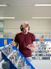 Spoed Foto op Canvas Muziekwinkel guy listening music in cd store