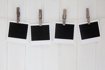 4 Polaroid vor weißer Holzwand